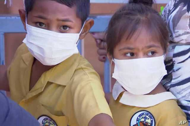 FILE - Children, their faces covered with masks, wait to get vaccinated against measles at a health clinic in Apia, Samoa, Nov. 18, 2019.