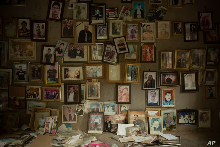 In this Sept. 12, 2019 photo, pictures of Yazidis slain in 2014 by Islamic State militants are found in a small room at the…