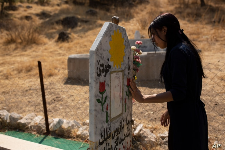 In this Sept. 13, 2019 photo, Layla Taloo visits the grave of a Yazidi woman who took her own life after she was captured by…