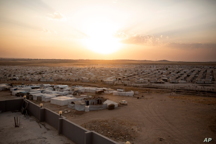 In this Aug. 24, 2019 photo, the sun sets over Sharia Camp, where Yazidis displaced by Islamic State militants are housed near…
