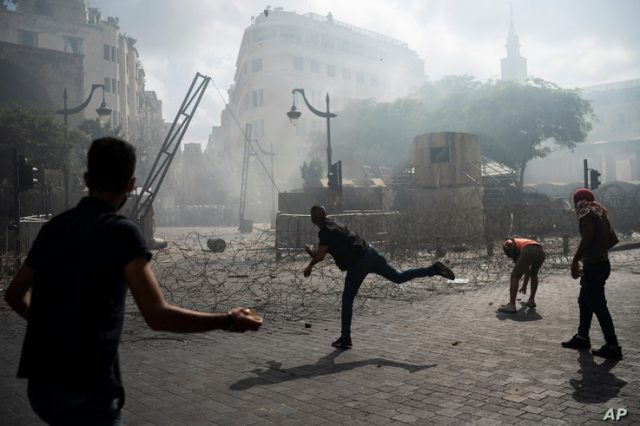 People clash with police during a protest against the political elites and the government after this week's deadly explosion at Beirut port which devastated large parts of the capital and killed more than 150 people, in Beirut, Lebanon, Aug. 8, 2020.