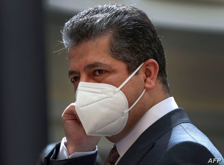 Prime Minister of the Regional Government of Iraqi Kurdistan Masrour Barzani adjusts his protective mask as he waits for the…