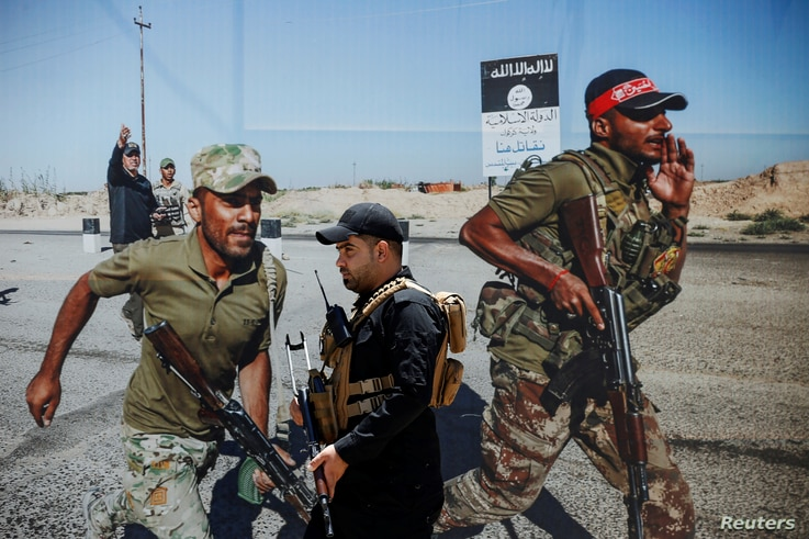 A members of Iraqi Popular Mobilization Forces (PMF) walks past a poster of PMF members at Popular Mobilization Forces Media…