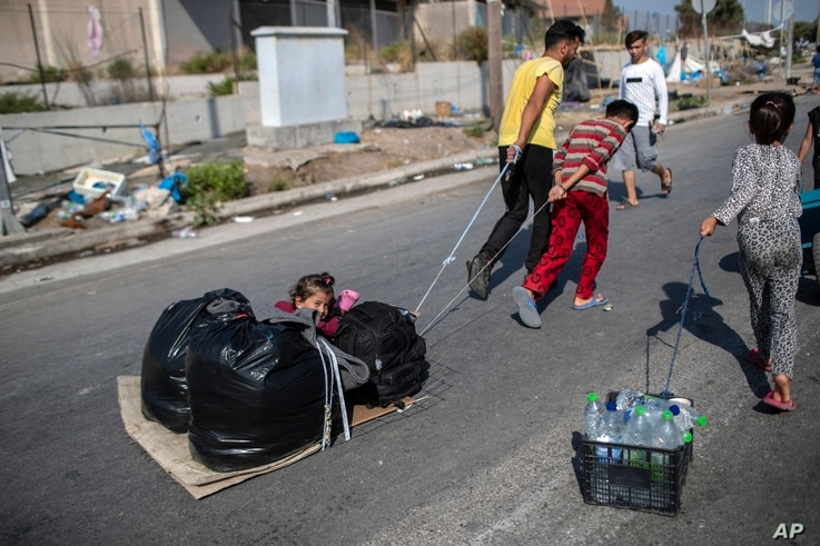A child sits between plastic bags as migrants pull their belongings in Kara Tepe, near Mytilene the capital of the northeastern…