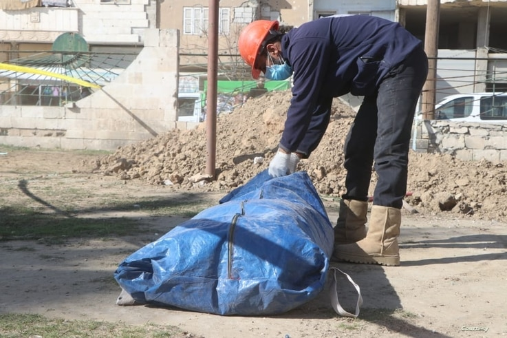 A member of The First Responders team in Raqqa seals a bag containing a body recovered from a mass graves. The exhuming operation use primitive means, as the team lacks technology to analyze the remains. (Photo: Osama al-Khalaf)