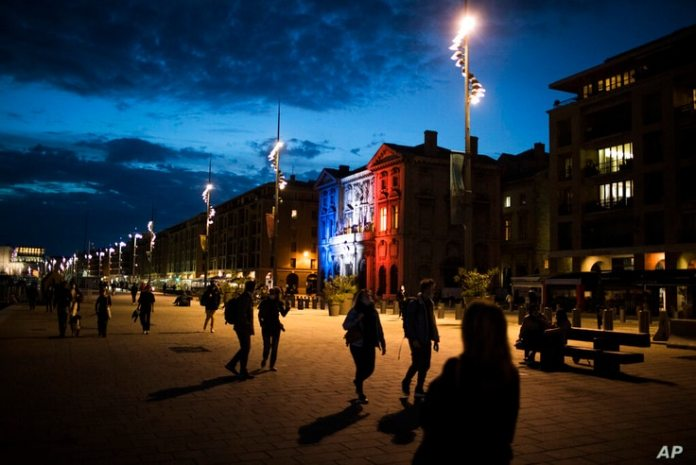 Pedestrians walk along the Old Port of Marseille while the town hall is illuminated in French tricolor to honor the murdered professor Samuel…
