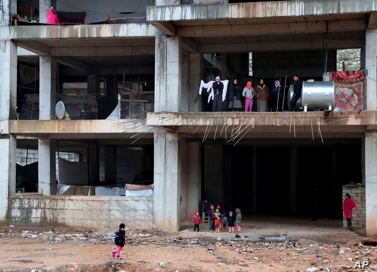 In this Wednesday, Dec. 10, 2014 photo, Yazidi families displaced by Islamic State group militants take shelter in a partially…