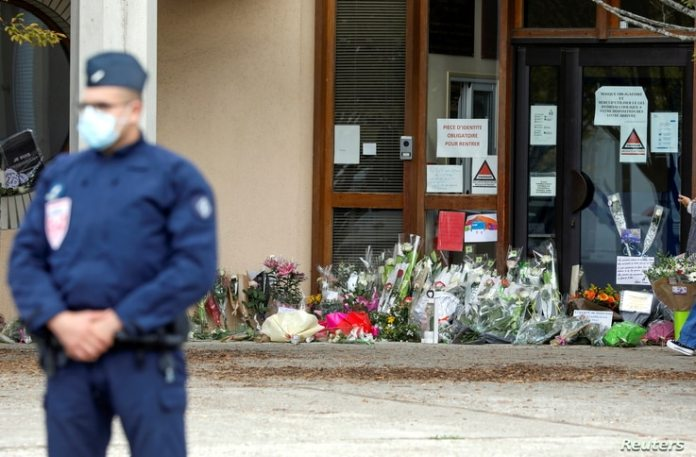 Flowers are stacked outside the school where murdered history teacher Samuel Paty worked, in Conflans-Sainte-Honorine, northwest of Paris, France, October 17, 2020.