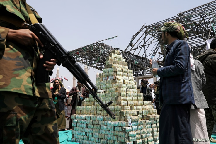Houthi followers stand by bills of Yemeni currency during a ceremony held by Houthis to collect supplies for their fighters…