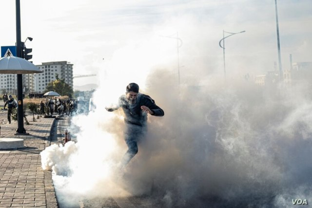 A protester runs through teargas as Kurdish security forces approach during anti-government demonstrations in the Iraqi Kurdistan city, Sulaymaniyah on Dec. 11, 2020. (Rebaz Majeed/VOA)