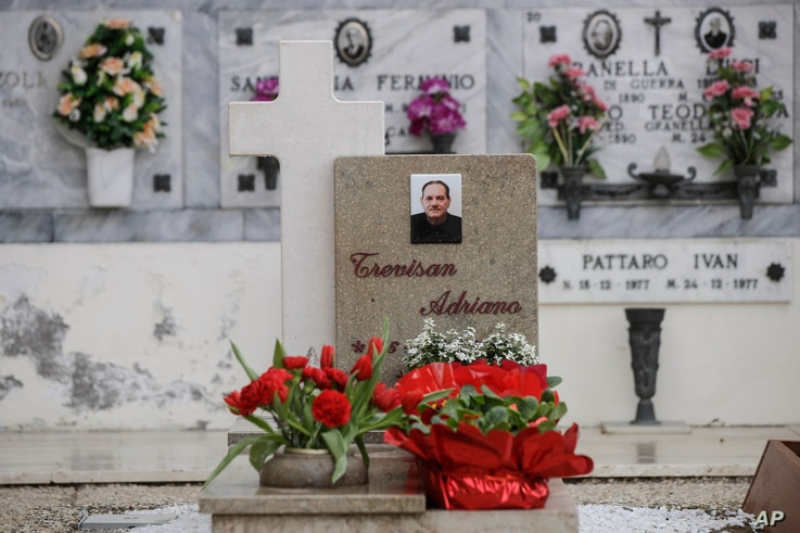 Flowers adorn the tombstone of Adriano Trevisan, Italy's first known victim of COVID-19, at the cemetery of Vo Vecchio, in Vo Euganeo, Feb. 10, 2021.