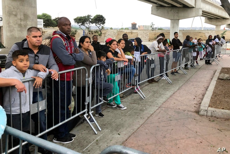 FILE - Asylum seekers in Tijuana, Mexico, listen to names being called from a waiting list to allow them an opportunity to make their case, at a border crossing in San Diego, California, Sept. 26, 2019.