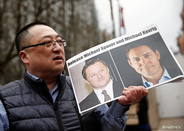 Louis Huang holds a placard ccalling for China to release Canadian detainees Michael Spavor and Michael Kovrig outside a court…
