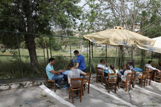 A waiter serves a group of people in a restaurant of Plaka district, as restaurants and cafes in Greece open after six months…