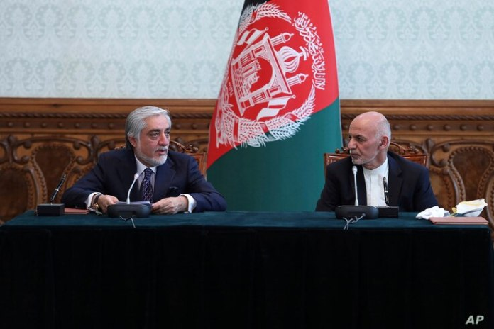 FILE - Afghanistan's President Ashraf Ghani, right, and his then-political rival Abdullah Abdullah speak after signing a power-sharing agreement at Rashtrapati Bhavan in Kabul, Afghanistan May 17, 2020.