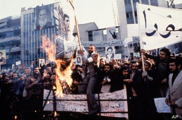 FILE - In an undated photo from 1979, protestors burn an effigy of Shah Mohammad Reza Pahlavi during a demonstration in front…