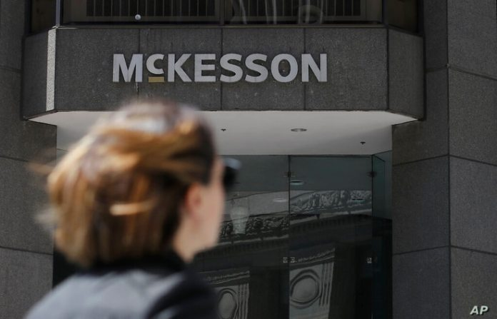 FILE - In this July 17, 2019, file photo, a pedestrian passes a McKesson sign at an office building in San Francisco.  The…