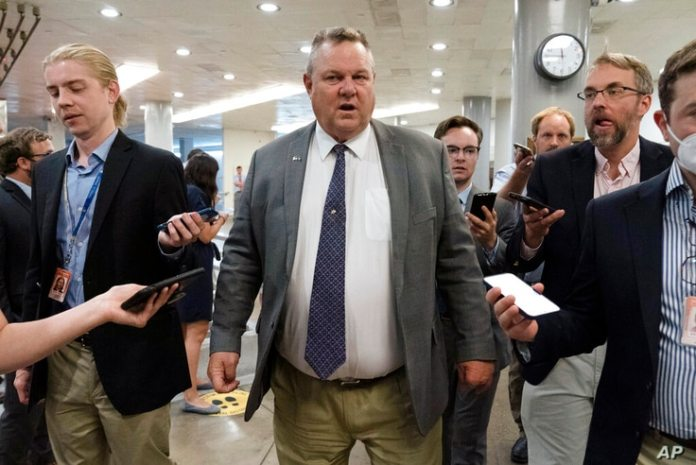 Sen. John Tester, D-Mont., talks to reporters as he walks into the Senate chamber ahead of a test vote set by Democratic...