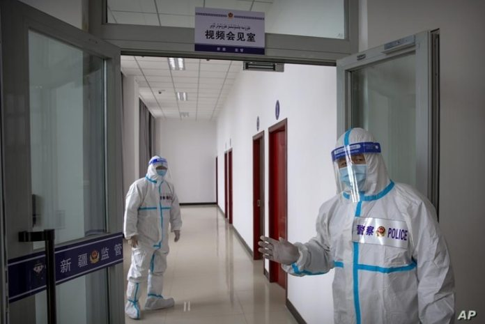 Security officers in protective suits stand in a hallway with rooms for video meetings with prisoners at the visitors' hall at the Urumqi No. 3 Detention Center in Dabangcheng in western China's Xinjiang Uyghur Autonomous Region on April 23, 2021.