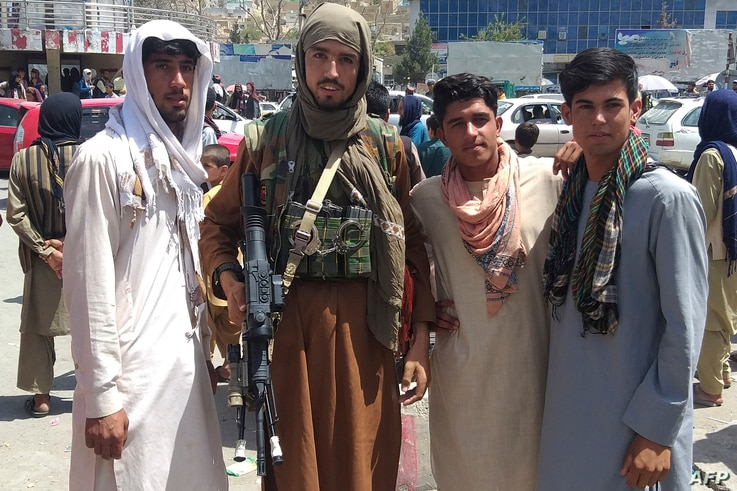 A Taliban fighter (2L) is seen with locals at Pul-e-Khumri on August 11, 2021 after Taliban captured Pul-e-Khumri, the capital…