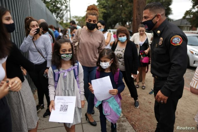 8-year-old Nicole Tschabourian (left) and 8-year-old Leah Yousefi arrived with a printed barcode on the first day of school, and returned full day after the COVID-19 outbreak in Glendale, California, on August 19 System face-to-face learning.  January 18, 2021.