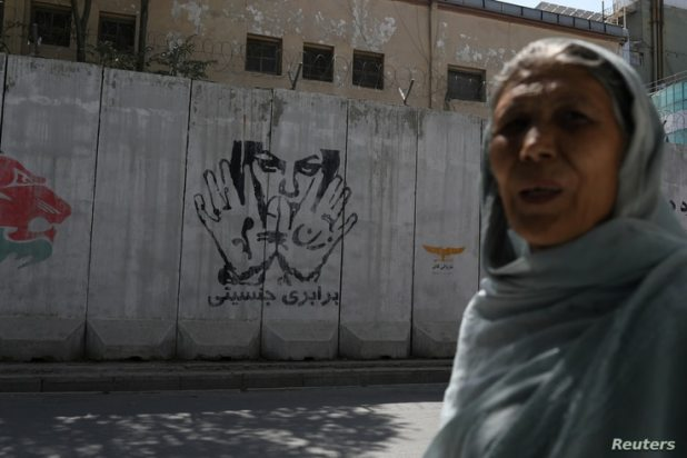 A mural promoting gender equality is seen in Kabul, Afghanistan, Sept. 4, 2021, as a woman passes by it. It will likely be replaced with black and white messages celebrating the Taliban and their ideology.