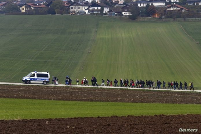 File - October 20, 2015, German police take immigrants to a registration center after crossing the Austrian-German border in Wegshed, near Passau, Germany.