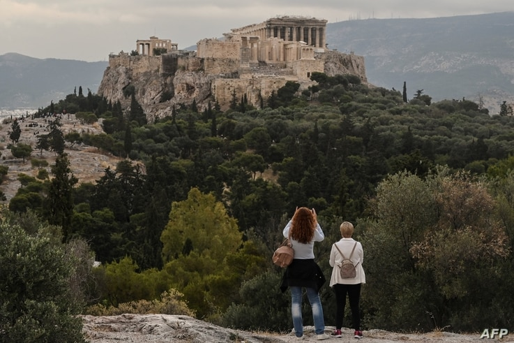 People visit the Pnyx Hill in Athens overlooking the ancient Acropolis on May 29, 2020 as Greece eases lockdown measures taken…