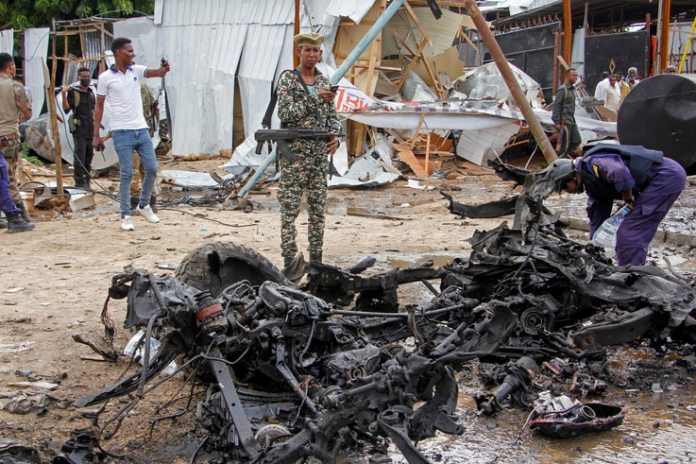 Security forces stand next to wreckage at the scene of a suicide car bomb attack in the capital Mogadishu, Somalia Monday, July…