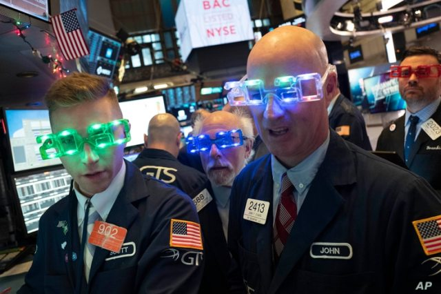 Stock traders wear New Year's 2020 party glasses at New York Stock Exchange, Tuesday, Dec. 31, 2019. Stocks slipped globally in…
