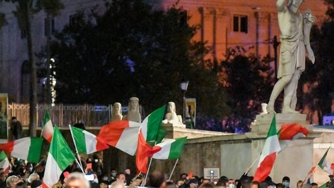 People wave Italian flags as they protest against the government restriction measures to curb the spread of Covid-19 in Rome,…