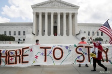 FILE PHOTO: DACA recipients and their supporters celebrate outside the U.S. Supreme Court after the court ruled in a 5-4 vote…