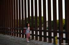 A young girl, part of a group of Central American migrants seeking asylum, walks along a stretch of border fence after…