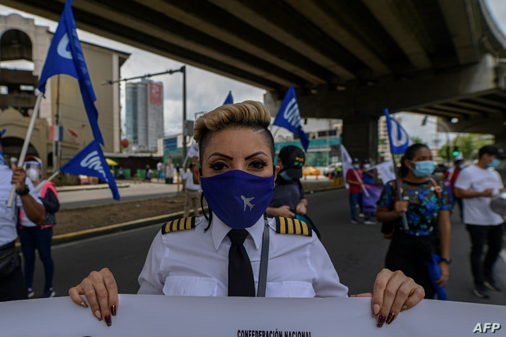 Employees of Copa Airlines take part in a protest against alleged corruption and hunger amid the new coronavirus pandemic…