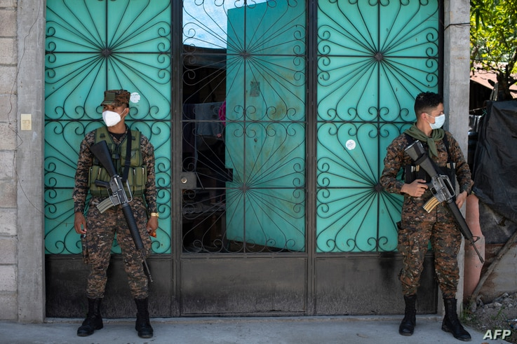 Soldiers from the Salvadoran air force paratrooper battalion stand guard at the December 1 community in Soyapango, El Salvador,…