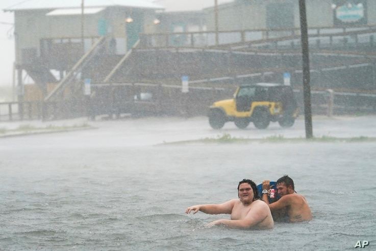 People play in a flooded parking lot at Navarre Beach, Tuesday, Sept. 15, 2020, in Pensacola Beach, Fla. Hurricane Sally is…
