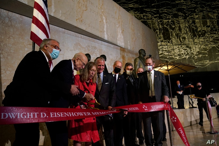 Members of the Eisenhower Memorial Commission cut a ribbon at the Eisenhower Memorial dedication ceremony in Washington,…