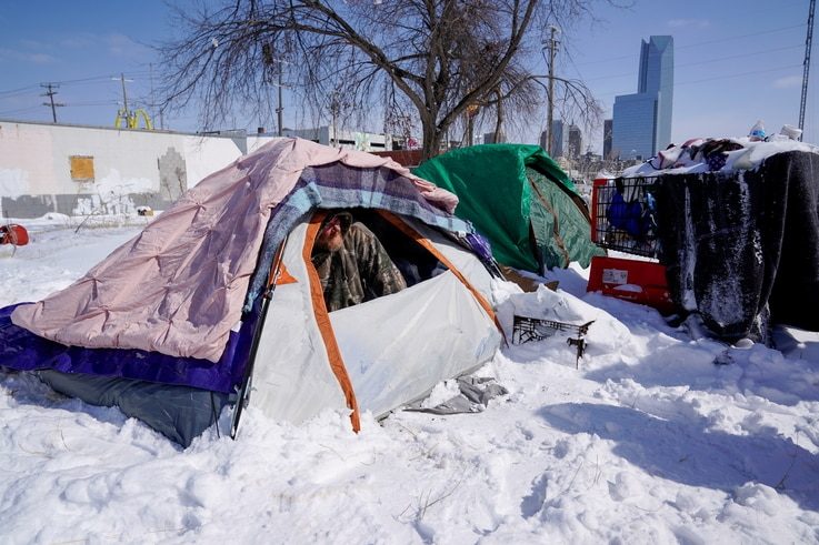 James Derrick, who is suffering from homelessness, peeks out of his tent during record breaking cold weather in Oklahoma City,…