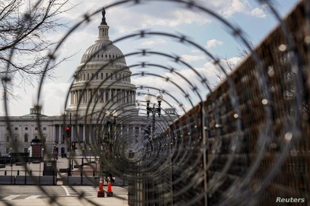 The U.S. Capitol is seen through razor wire after police warned that a militia group might try to attack the U.S. Capitol in…