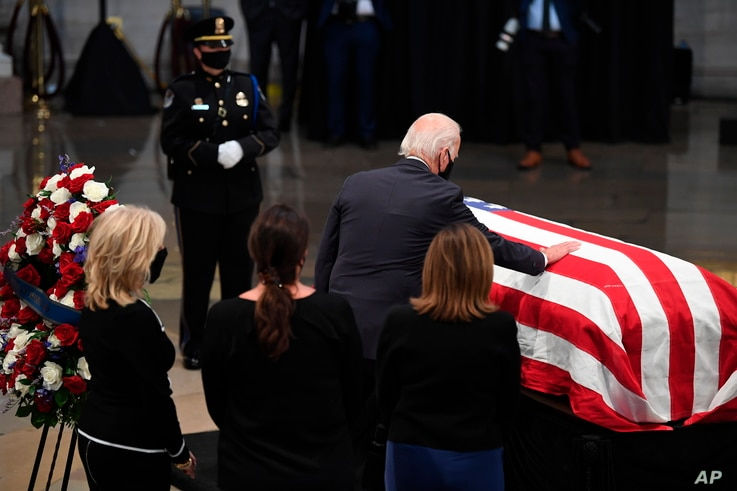 Democratic presidential candidate, former Vice President Joe Biden, with Jill Biden, left, touches the flag-draped casket of…
