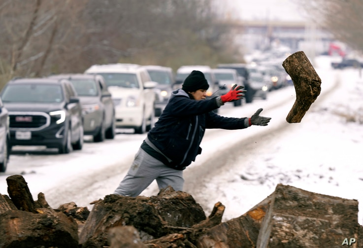 Michelle Terrazas tosses a log of firewood as as people line up to load up Wednesday, Feb. 17, 2021, in Dallas. (AP Photo/LM…