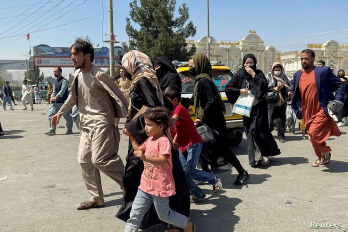 People try to get into Hamid Karzai International Airport in Kabul