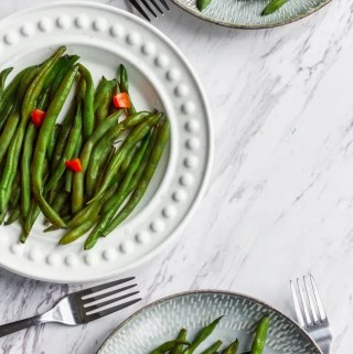 vegan green beans with diced red bell pepper on plate with fork