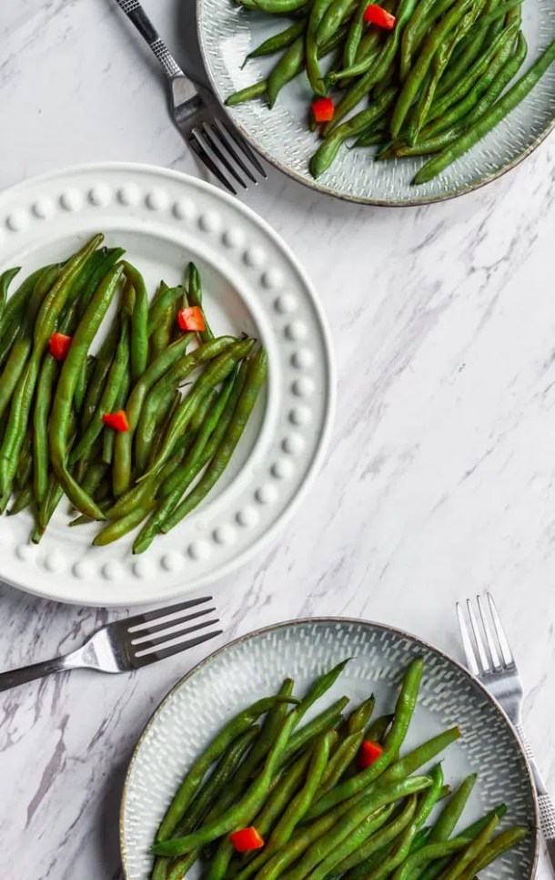 vegan green bean with diced red bell pepper on plate with fork