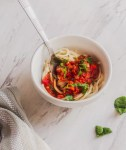 lentil bolognese in white bowl with fork topped with parsley