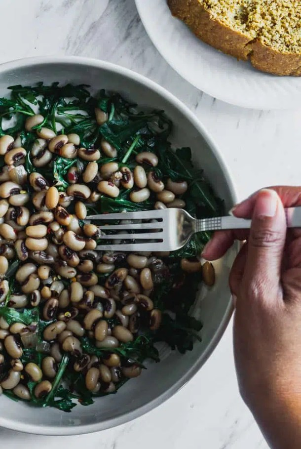 new years vegan black eyed peas over greens in bowl with cornbread on side
