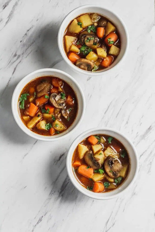white bowls of vegetables stew filled with mushrooms, potatoes and carrots