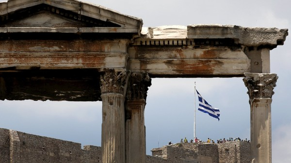 The Greek flag is framed by the arch of Hadrian atop the Acropolis hill in Athens, Greece June 26, 2015. The leaders of Germany and France offered to release billions in frozen aid on Friday in a last-minute push to talk Greek Prime Minister Alexis Tsipras into contentious pension reforms in exchange for filling Athens' empty coffers until November. REUTERS/Yannis Behrakis
