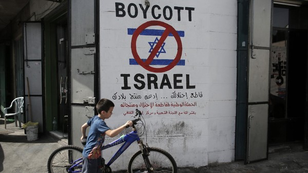 A Palestinian boy walks with his bicycle past past a mural calling people to boycott Israeli goods in the al-Azzeh refugee camp near the West Bank city of Bethlehem on September 17, 2014. There have been growing calls for an economic, academic and cultural boycott of Israel over alleged human rights violations, including in Gaza, where a recent 49-day conflict has killed more than 2,100 Palestinians, most of them civilians. AFP PHOTO/ AHMAD GHARABLI (Photo credit should read AHMAD GHARABLI/AFP/Getty Images)