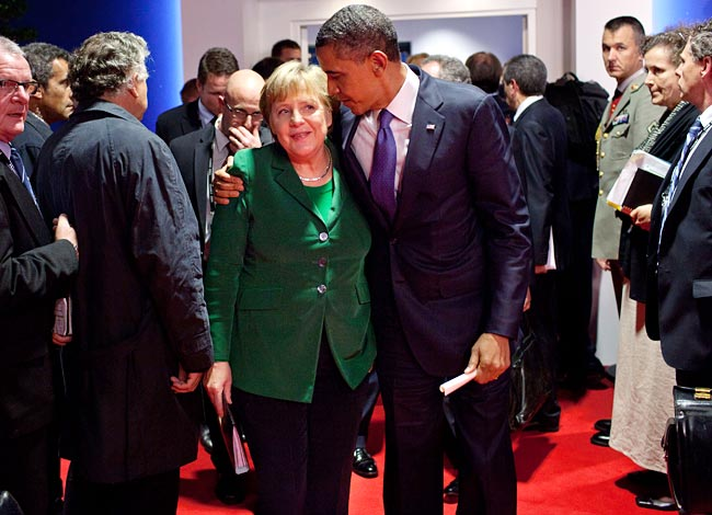 Making up: Barack Obama attempts to comfort Angela Merkel after a fractious meeting
